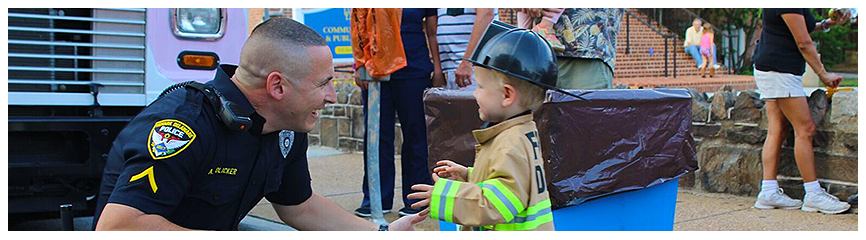 Police officer giving a hug to a child in a fire fighter's uniform